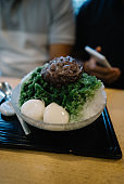Delicious shave ice with matcha syrup, topped with red bean and mochi