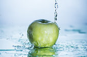 Green apple with freezed water splash