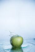 Green apple with freezed water splash