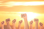 Hand of people arm raising up showing power strong with sky at sunrise background .success concept