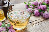 Red clover flowers, healthy herbal tea cup, honey jar and vintage copper tea kettle on table.