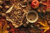 Coffee, apple and walnut on table