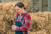 Female farmer typing sms message on mobile phone