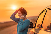 Woman talking on mobile phone by the stopped car