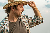 Worried farmer standing in ripe cultivated barley field