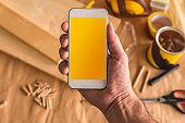 Small business woodwork entrepreneur holding modern smartphone