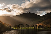 Majestic vibrant Autumn Fall landscape Buttermere in Lake District with beautiful early morning sunlight playing across the hills and mountains