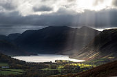 Majestic sun beams light up Crummock Water in epic Autumn Fall landscape image with Mellbreak and Grasmoor