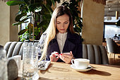 Beautiful attractive business woman holding mobile phone in cafe. Coffee break