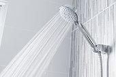 Water running from shower head and faucet in modern bathroom.