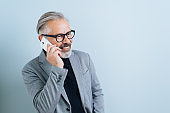 Businessman smiling as he chats on a mobile phone