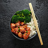 Teriyaki chicken, steamed broccoli and basmati rice served in bowl with chopsticks