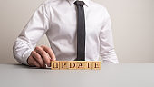 Businessman making an Update sign of wooden cubes