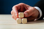 Businessman placing three blank wooden dices in a pyramid shape