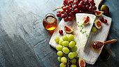 Cheese brie with figs, green and red grape and honey on white wooden board