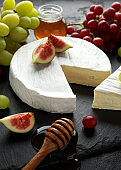 Stone Plate of white cheese brie with figs, green and red grape and honey.