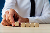 Businessman placing five blank wooden dices in a row