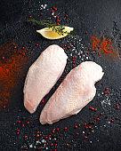 Raw duck breast with seasonings on rustic black background