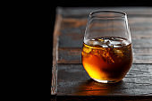 Glass of whiskey with ice on rustic table