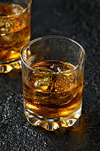 Glass of whiskey with ice on rustic background