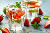Strawberry Mojito cocktail with Rum, lime and mint in glass. Summer cold drink with ice