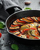 Ratatouille Vegetable Stew with zucchini, eggplants, tomatoes, garlic, onion and basil. on cast iron pan. Traditional French food.