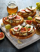 This Fig and Gorgonzola tartines, toast, bruschetta. drizzled with honey on white wooden board