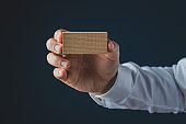 Businessman holding blank wooden peg showing it to the camera