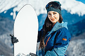 Close up of snowboard girl smiling and posing on mountain and slope background.