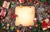 Frame with vintage paper, fir branches, cookies and Christmas decorations on dark wooden background.