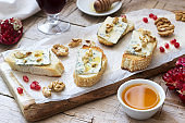 Sandwiches with blue cheese, pomegranate, honey and nuts served with red wine. Rustic style.