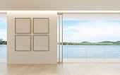 View of living room in minimal style with  picture frame on white wall and sea view background.. 3d rendering.
