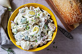 Traditional American potato salad with egg and mayonnaise, served with bread. Rustic style.