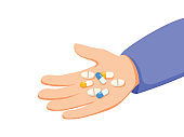 Human hand holds pile of pills and tablets isolated from background. Concept of medication treating illness or disorder.