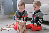 Twins boys brothers are building from wooden blocks sitting on the floor by the sofa in their room.