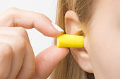 Young woman's fingers putting yellow earplug into her ear on light gray background. Closeup.