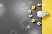 Creativity inspiration, great business idea concept with white light bulb and paper crumpled ball on gray and yellow background. Flat lay, top view, copy space