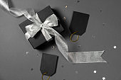 Gift box wrapped in black paper with silver ribbon, stars confetti and price tags on bright gray background. Copy space and top view. Black friday box gift present isolated.