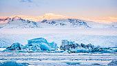 Icebergs float on Jokulsarlon glacier lagoon at sunrise
