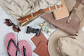 Prepare for journey in africa style - accessories and travel items, packing clothes in backpack: backpack, hat, passport, flip flops, sunglasses, compass