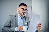Beautiful caucasian classy smiling businessman in suit and with eyeglasses holding in one hand coffee and in other document and looking at it. On desk are laptop and paperwork. Office interior.