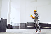Well dressed architect in gray suit and with protective helmet on head reading documents while going to site.