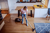 Top view of cheerful caucasian blond young housewife dressed casual using vacuum cleaner to clean floor in living room.