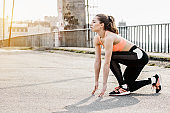 Focused sports woman standing on starting position before sprint