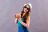 Cheerful girl posing with coconut in hands and smiling