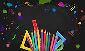 Back to school banner template design with frame from realistic colorful pencils, measure rulers, protractors isolated on abstract black blackboard background with paint splashes and school supplies