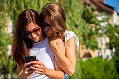Female friends looking at mobile phone by the river