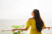 Portrait beautiful young asian woman smile happy and relax at outdoor balcony with sea beach and ocean view