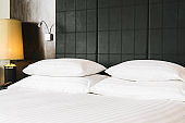 Beautiful luxury comfortable white pillow and blanket on bed with light lamp