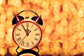 New year's eve midnight. Retro alarm clock whose pointer shows five to twelve on festive bokeh background